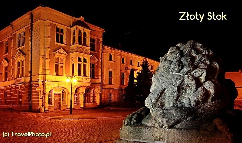 Złoty Stok - pomnikowy lew, w tle kamienica Guttmanów